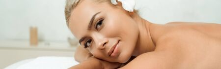 panoramic shot of attractive and smiling woman looking at camera and lying on massage table in spa