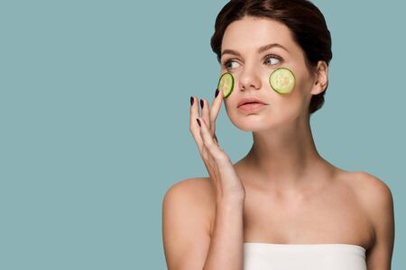 attractive woman touching cucumber on face isolated on blue Archivio Fotografico - 134811122