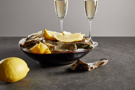 selective focus of delicious oysters and lemons in bowl near champagne glasses with sparkling wine isolated on grey Zdjęcie Seryjne