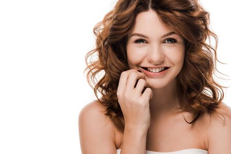 cheerful curly girl smiling and touching face isolated on white Archivio Fotografico - 134811406