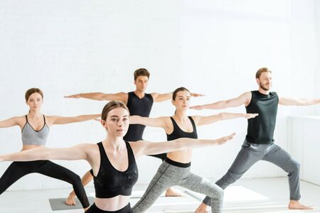 five young people practicing yoga in warrior II pose 스톡 콘텐츠