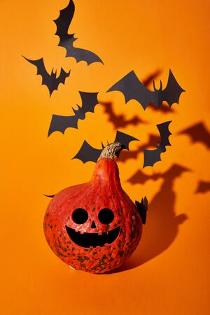 smiling pumpkin and paper bats with shadow on orange background, Halloween decoration Stock fotó