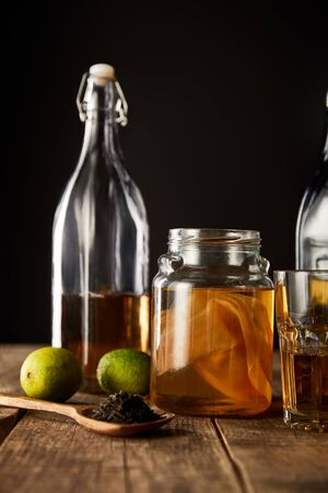 glass jar with kombucha near lime, spice and bottle on wooden table isolated on black Stock Photo