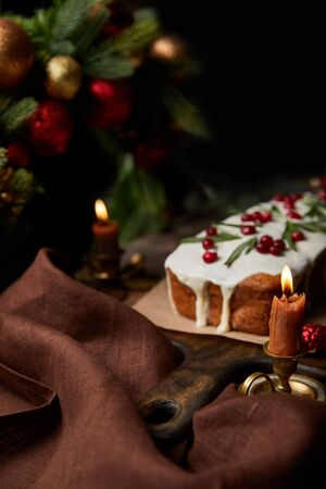 selective focus of traditional Christmas cake with cranberry near burning candles on wooden table