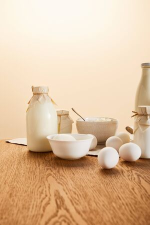 tasty organic dairy products and eggs on rustic wooden table isolated on beige