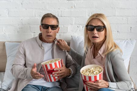 Shocked couple in 3d glasses and buckets with popcorn on bed 版權商用圖片