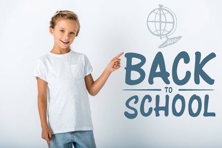 cheerful kid looking at camera and pointing with finger at back to school letters on white