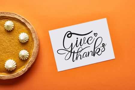 top view of pumpkin pie and card with give thanks illustration on orange background 版權商用圖片
