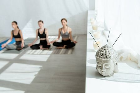 selective focus of Buddha head sculpture with aromatic sticks on windowsill, and three women sitting in half lotus pose