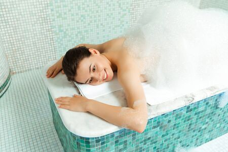 high angle view of smiling woman lying on hammam table with foam in turkish bath 版權商用圖片