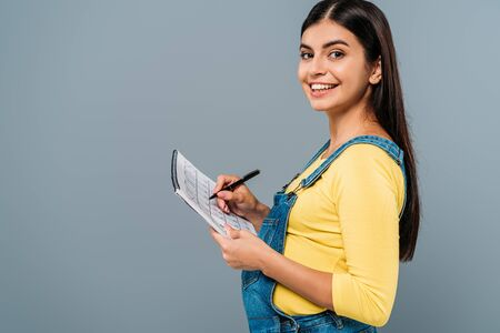 side view of smiling pregnant pretty girl holding period calendar and pen isolated on grey