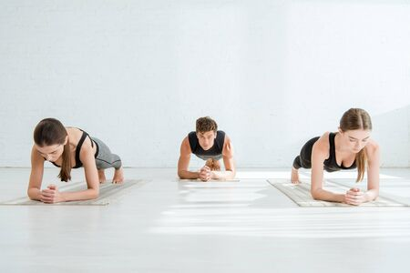 young women and man practicing yoga in forearm plank pose