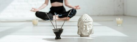 cropped view of woman sitting in half lotus pose near buddha head sculpture, aromatic sticks and candles, panoramic shot