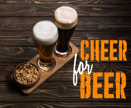 glasses of dark and light beer near bowl with roasted peanuts on wooden table with cheer for beer lettering