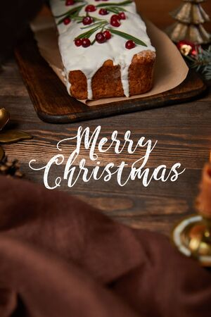 traditional Christmas cake with cranberry on wooden table with brown napkin and white merry Christmas lettering