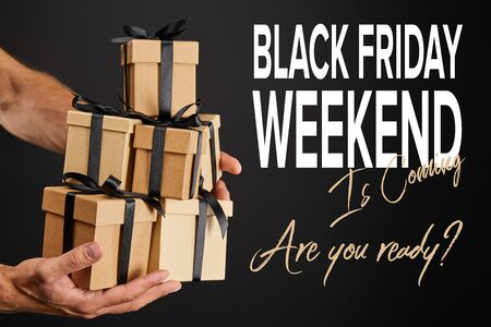 cropped view of man holding cardboard gift boxes with ribbons isolated on black with black Friday weekend illustration
