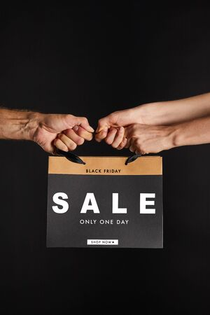 partial view of woman and man holding paper shopping bag with sale only one day illustration isolated on black, black Friday concept
