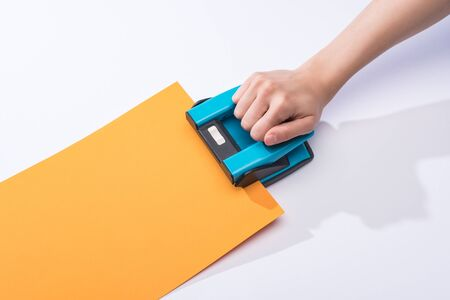 cropped view of woman using holepunch on white background 版權商用圖片 - 134811542