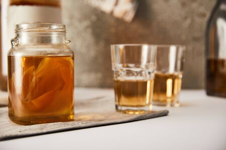 selective focus of jar with kombucha near glasses on textured grey background