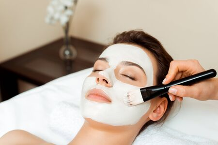 cropped view of cosmetologist applying face mask on attractive woman in spa 版權商用圖片 - 134811559