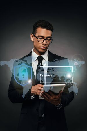 african american businessman in glasses using digital tablet on dark background with cyber security illustration