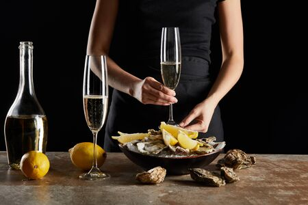 cropped view of woman holding glass with sparkling wine near oysters and lemons in bowl with ice isolated on black