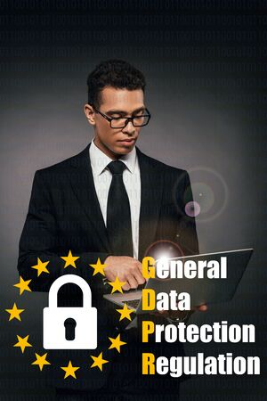 african american businessman using laptop on dark background with gdpr illustration Stock Photo