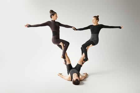 People in black sportswear practicing acroyoga