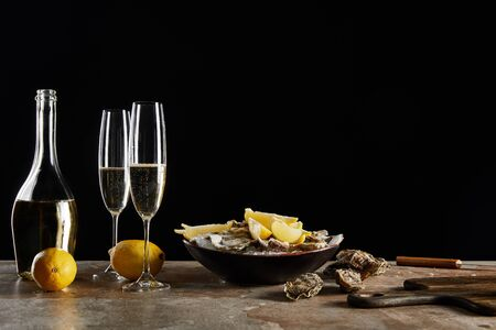 champagne glasses with sparkling wine near oysters and lemons in bowl isolated on black Zdjęcie Seryjne