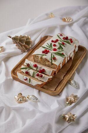 traditional Christmas cake with cranberry on wooden board near baubles on white cloth isolated on grey 版權商用圖片