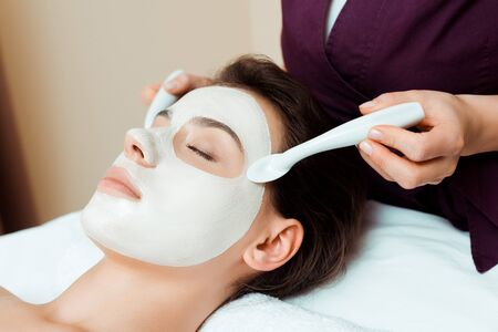 cropped view of cosmetologist applying face mask on attractive woman in spa Archivio Fotografico - 134811606