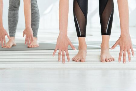 cropped view of barefoot women practicing halfway lift pose