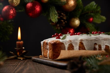 selective focus of traditional Christmas cake with cranberry near Christmas wreath with baubles and candle on wooden table isolated on black 版權商用圖片