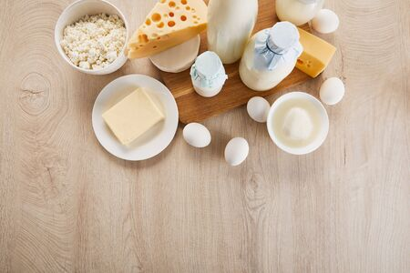 top view of various fresh organic dairy products and eggs on wooden table