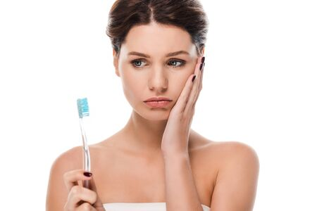 sad young woman touching face while holding toothbrush isolated on white Archivio Fotografico - 134811679