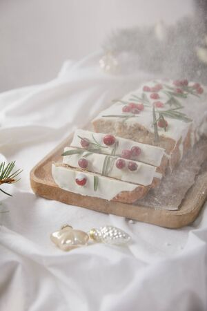 traditional Christmas cake with cranberry on wooden board near silver baubles and pine needles isolated on grey with falling snow
