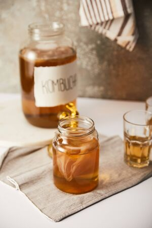 selective focus of jar with kombucha near glasses on textured grey background with striped napkin