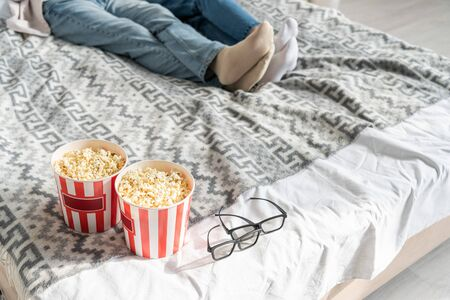 Cropped view of couple lying on bed beside popcorn buckets and 3d glasses