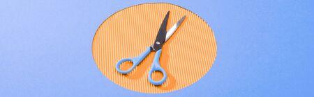 panoramic shot of metal scissors on orange circle