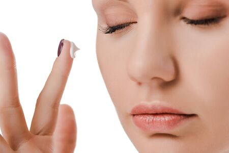 close up of woman with closed eyes and face cream on finger isolated on white