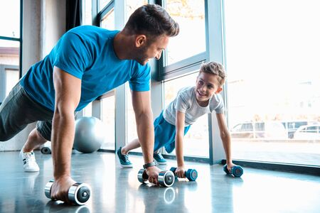 happy father looking at cheerful son and exercising with dumbbells Zdjęcie Seryjne