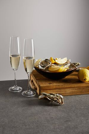 oysters and fresh lemons in bowl near champagne glasses with sparkling wine isolated on grey