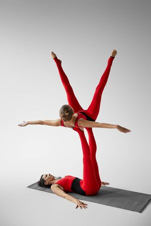 Two women practicing acroyoga on yoga mat in studio isolated on grey 스톡 콘텐츠