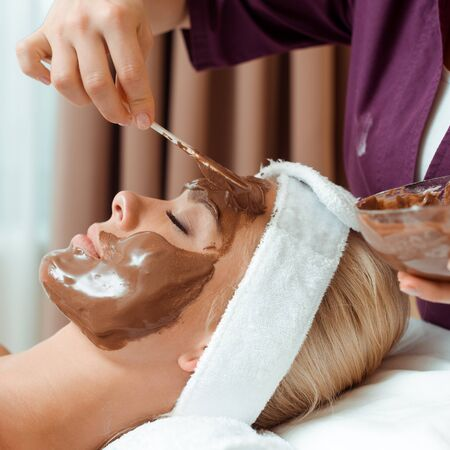cropped view of cosmetologist applying face mask on attractive woman in spa Archivio Fotografico - 134811784
