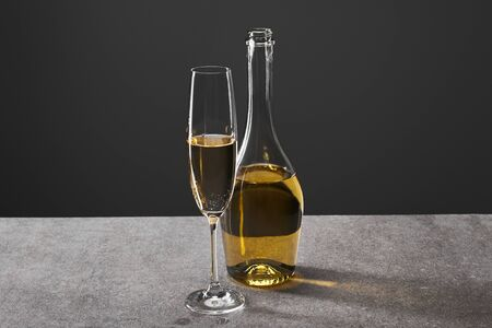 glass and bottle of champagne for celebrating christmas on grey