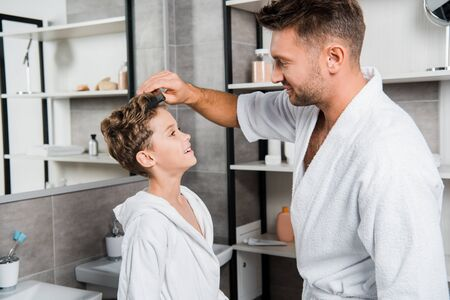 handsome father brushing hair of cute son in bathroom