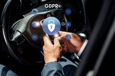 partial view of african american businessman in suit using smartphone with gdpr illustration in car at sunny day Stock Illustration - 134811793