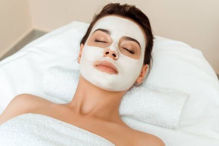 high angle view of attractive woman with mask on face lying on massage table in spa Archivio Fotografico - 134811794