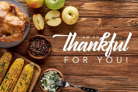 top view of roasted turkey and grilled corn with apples served on wooden table with i am so thankful for you illustration Banco de Imagens