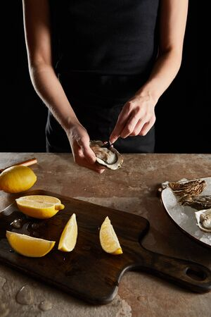 cropped view of chef holding fork near fresh oyster isolated on black